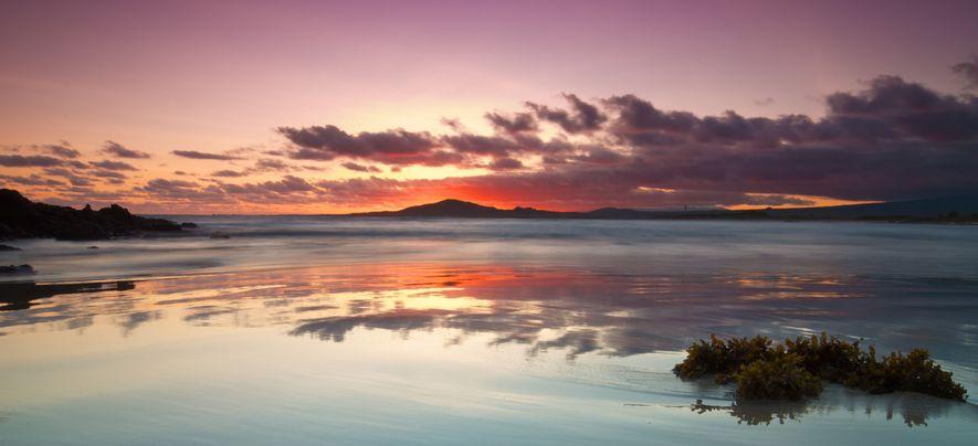 Sur la plage du Puerto Villamil, aux Galápagos, le coucher de soleil qui embrase la silhouette ...