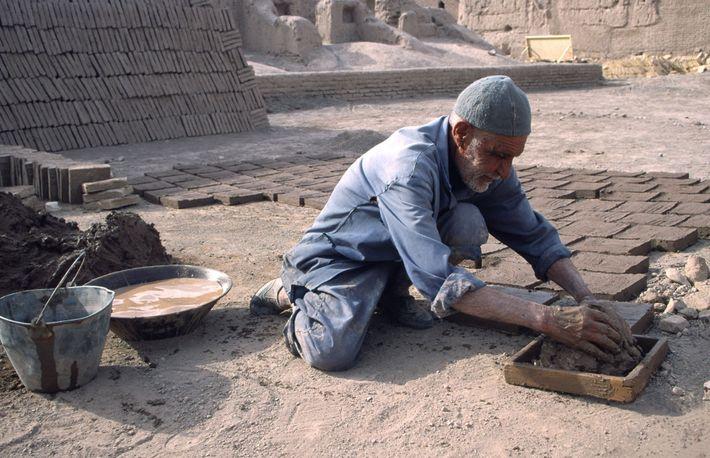 Un homme prépare le Khesht, brique de boue séchée au soleil.