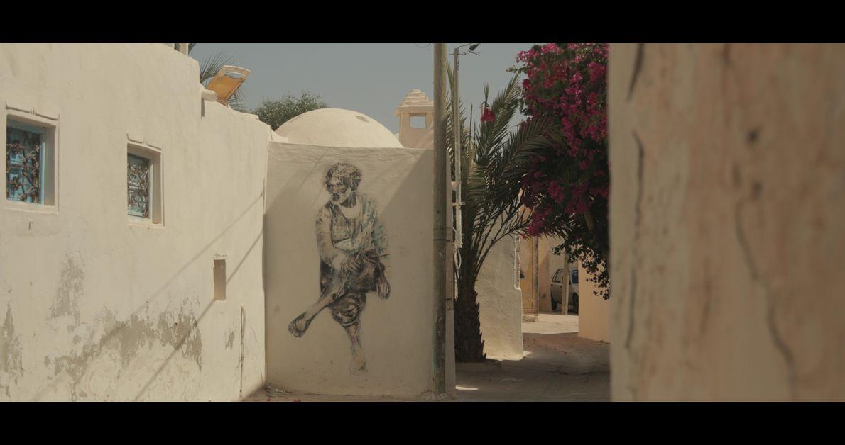 Au détour d'un chemin, le graffiti de Dabro observe les passant.e.s, « Djerbahood » - Erriadh, Tunisie, ...