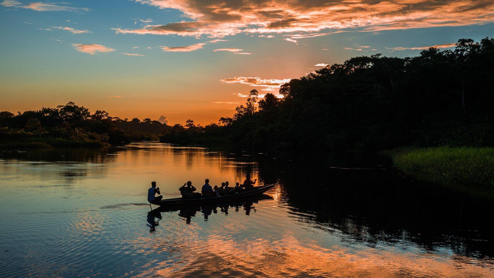 Dans la réserve de Yasuní, des touristes traversent en canoë le fleuve Amazone.