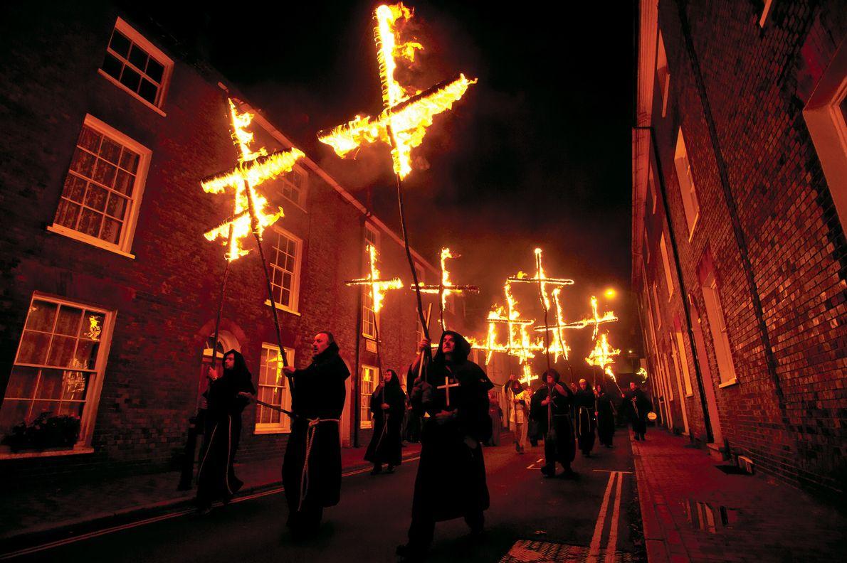 Lors d'une cérémonie organisée à Lewes, en Angleterre, les participants défilent avec des croix enflammées pour ...