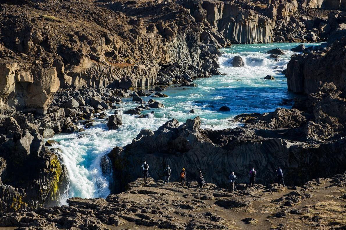 Des photographes prennent en photo la cascade d'Aldeyjarfoss alors que l'eau s'écrase sur les falaises rocheuses. ...
