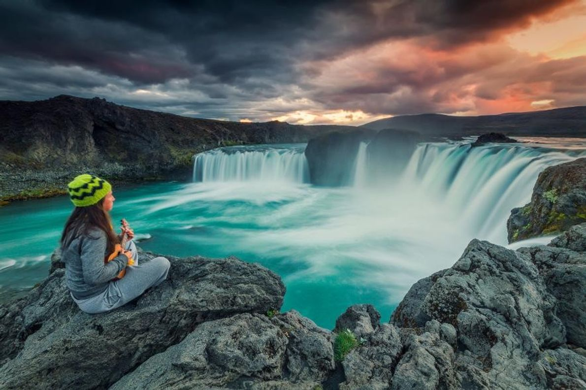 Une jeune femme joue du ukulele au sommet d'une falaise près des chutes d'eau de Goðafoss, ...