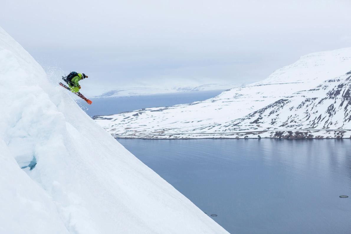 Un skieur dévale une piste dans dans les Fjords de l'Ouest, en Islande, une région dessinée ...