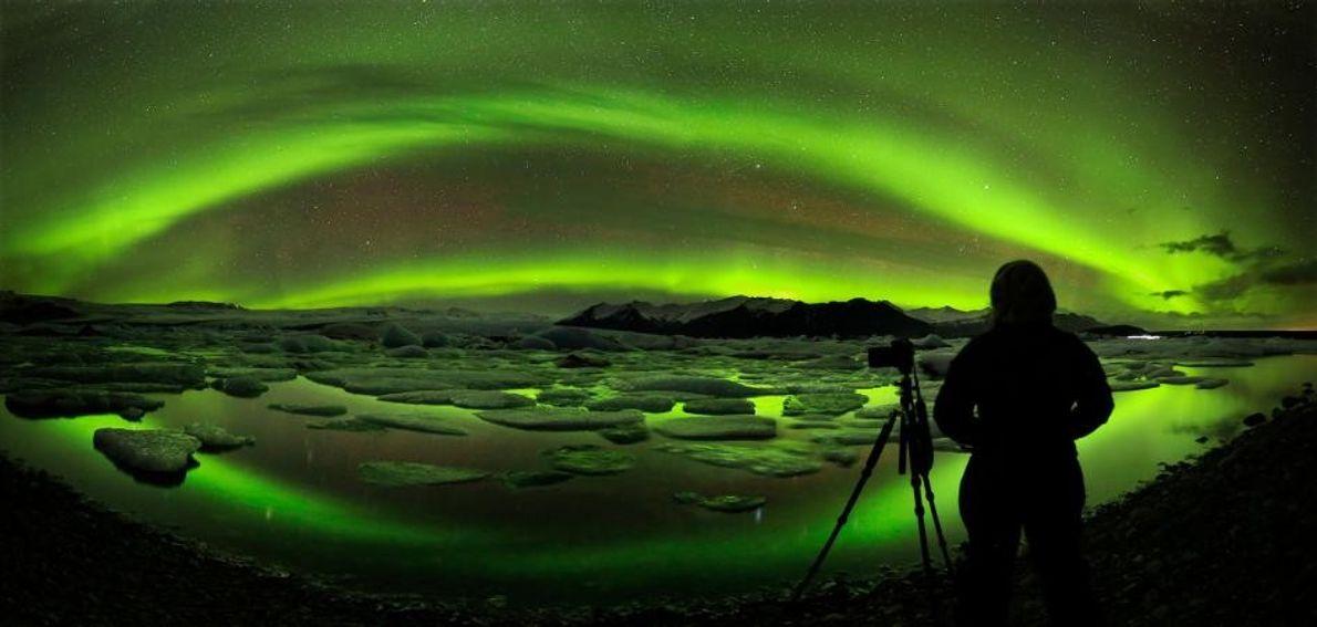 Un photographe tente de capturer la voûte d'une aurore boréale qui surplombe le glacier de Jökulsárlón. ...