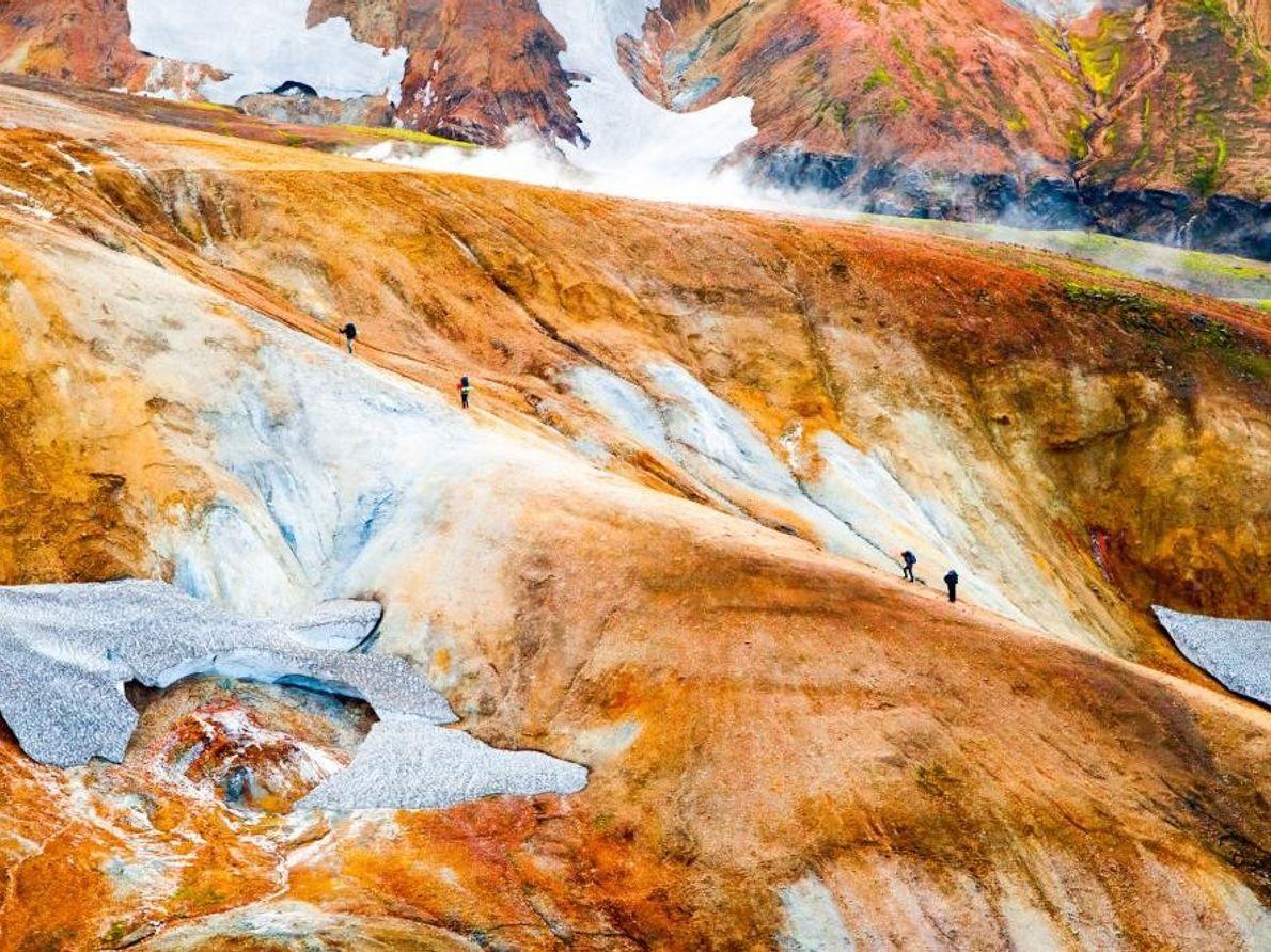 Des randonneurs parcourent le sentier de Landmannalaugar, une randonnée qui traverse des sources chaudes, des champs ...