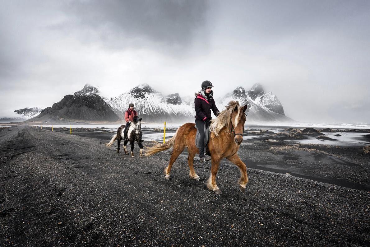 Des cavaliers voyagent à travers la montagne de Vestrahorn dans la péninsule de Stokksnes, sur la ...