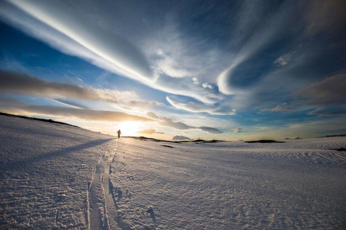 Le soleil brille devant une skieur de fond dans les Fjords de l'Ouest, en Islande.