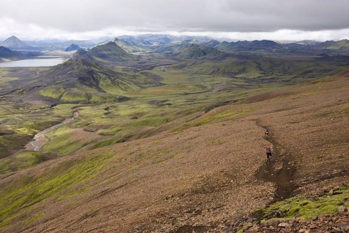Deux cyclistes tout terrain empruntent un chemin de terre et prennent la direction d'un des nombreux ...