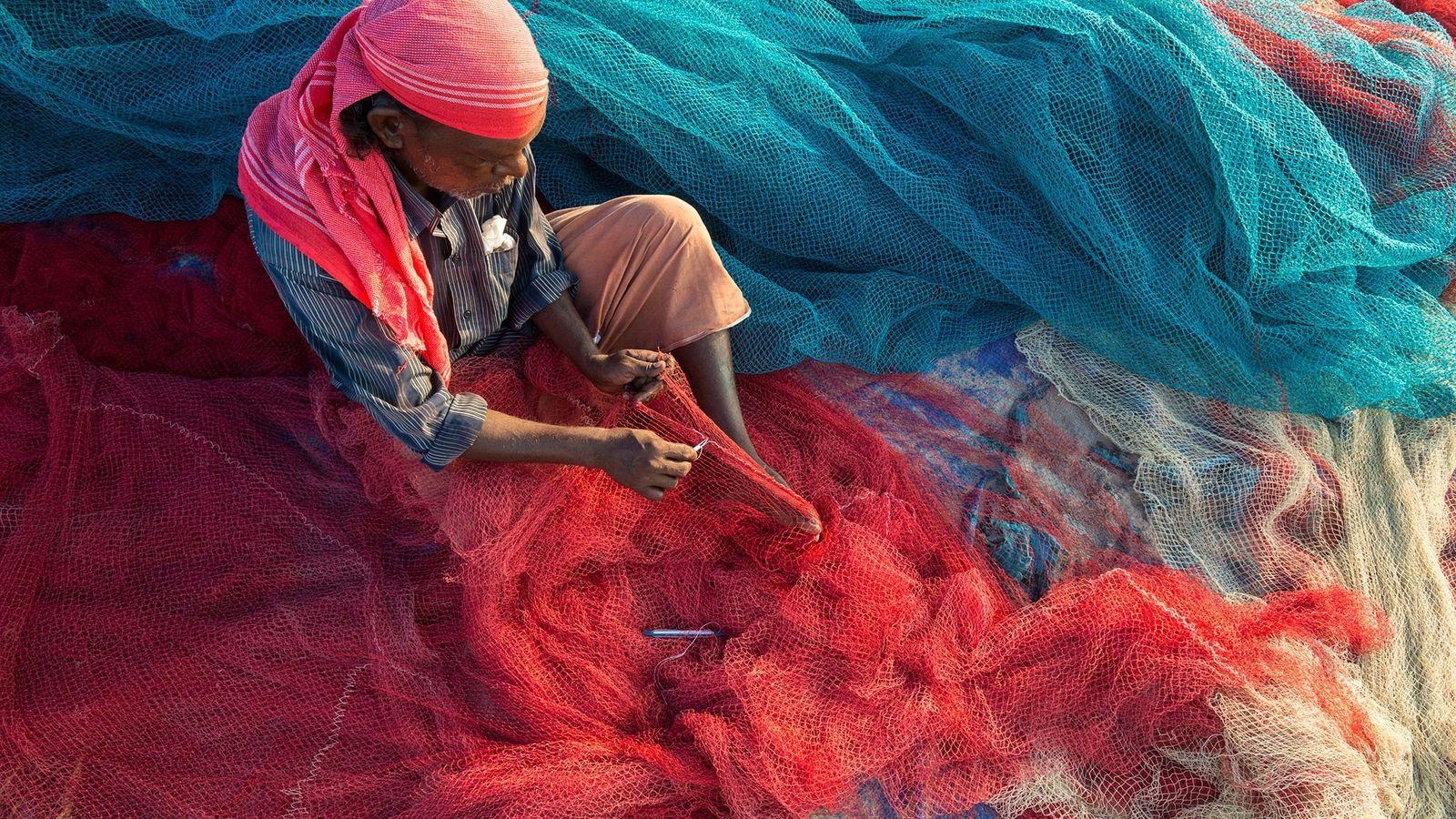 Dans l'État de Kérala en Inde, un pêcheur répare ses filets de pêche sur une plage. ...