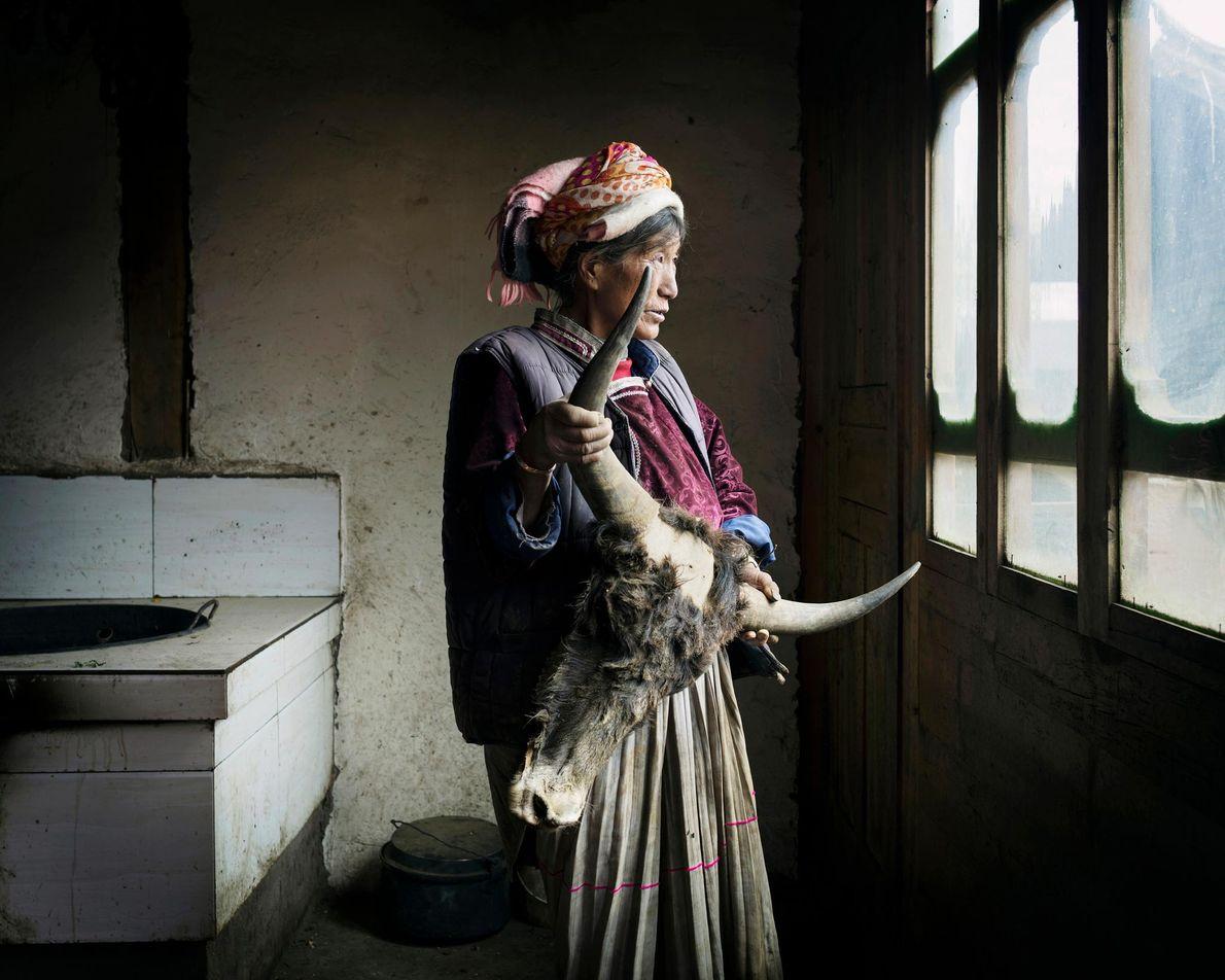 Asa Pure, 67 ans, originaire du village Shankua regarde par la fenêtre.