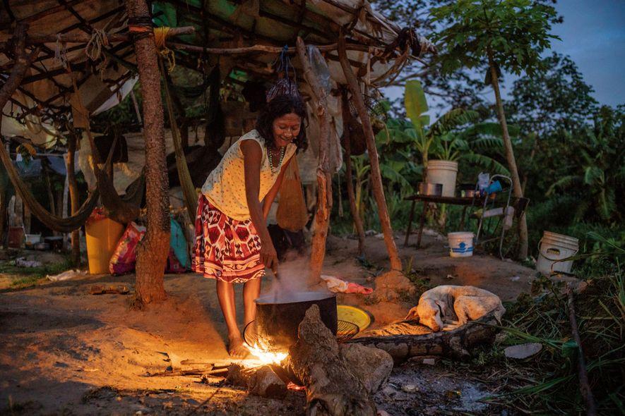 Une femme warao prépare à manger sur un feu de camp, près de Ciudad Guayana, au Venezuela, au bord de la route menant à la frontière. De nombreux Warao marchent ou font du stop pour trouver refuge au Brésil.