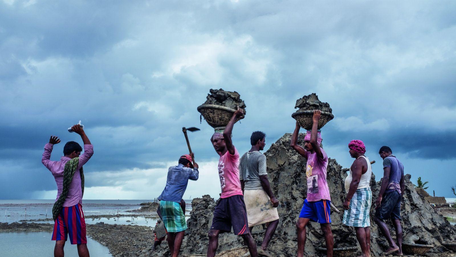 Des ouvriers réparent les digues en terre qui doivent protéger l'île de Sagar des inondations.