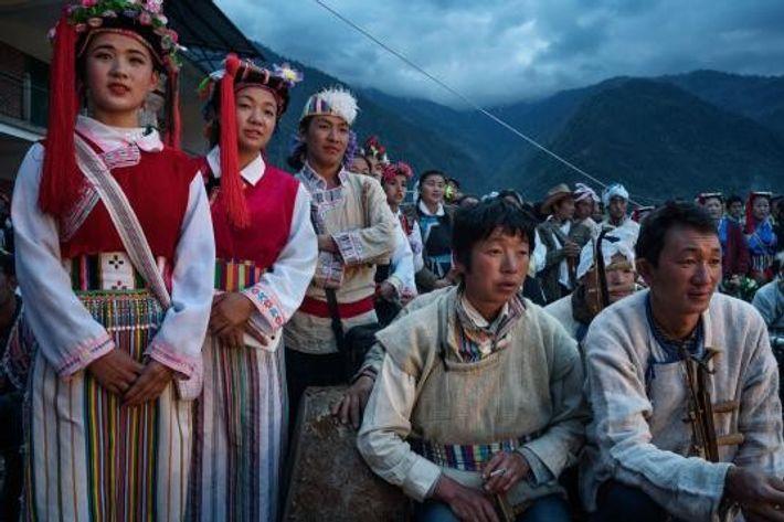 Des hommes et des femmes portent des costumes traditionnels et attendent de monter sur scène pour ...
