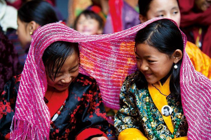 Dans la région de Bumthang, des fillettes assistent aux danses rituelles et aux pitreries des atsaras, ...