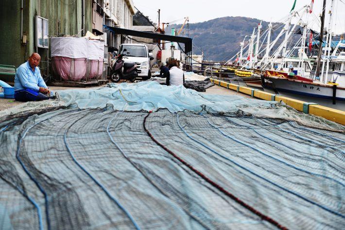 Séance de rafistolage de filets dans le petit port de Bōzejima, l'île des pêcheurs. Chaque matin ...
