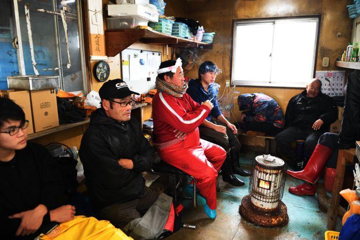 Les membres de l'association des pêcheurs attenden t le retour des bateaux, qu'ils aideront à décharger. ...