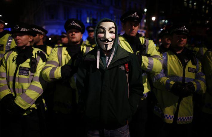 Un manifestant portant un masque de Guy Fawkes se tient devant une ligne de policiers anti-émeute ...