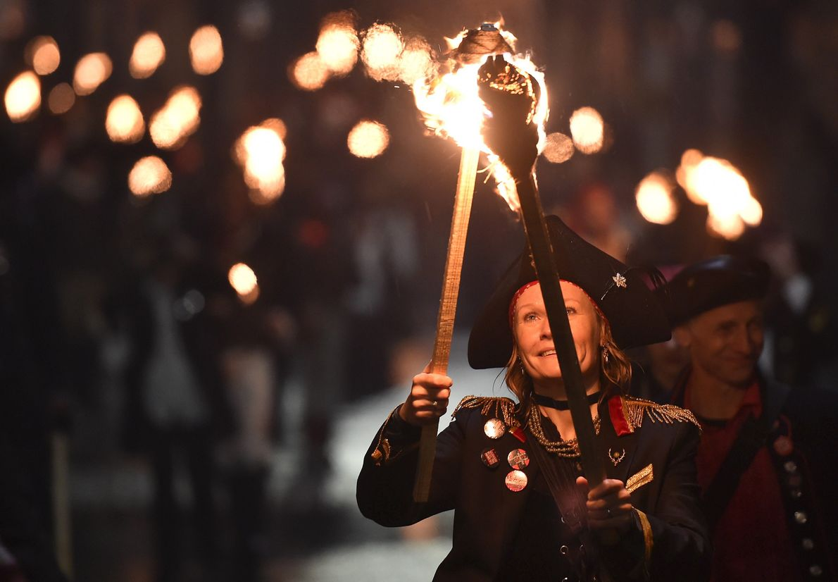 Les participants costumés brandissent des torches allumées lors de l'une des processions organisées dans le sud ...