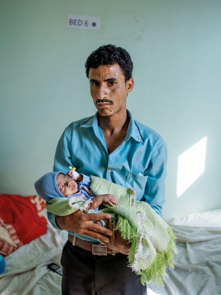 À l'hôpital Mère-Enfant de Taizz, un père tient dans ses bras son bébé soigné pour une ...