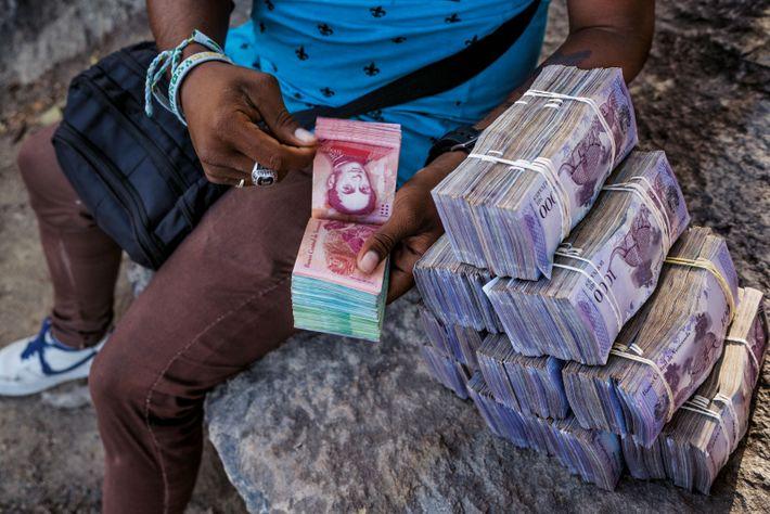 Du côté brésilien de la frontière, un changeur montre 5 millions de bolivars vénézuéliens. Une liasse ...