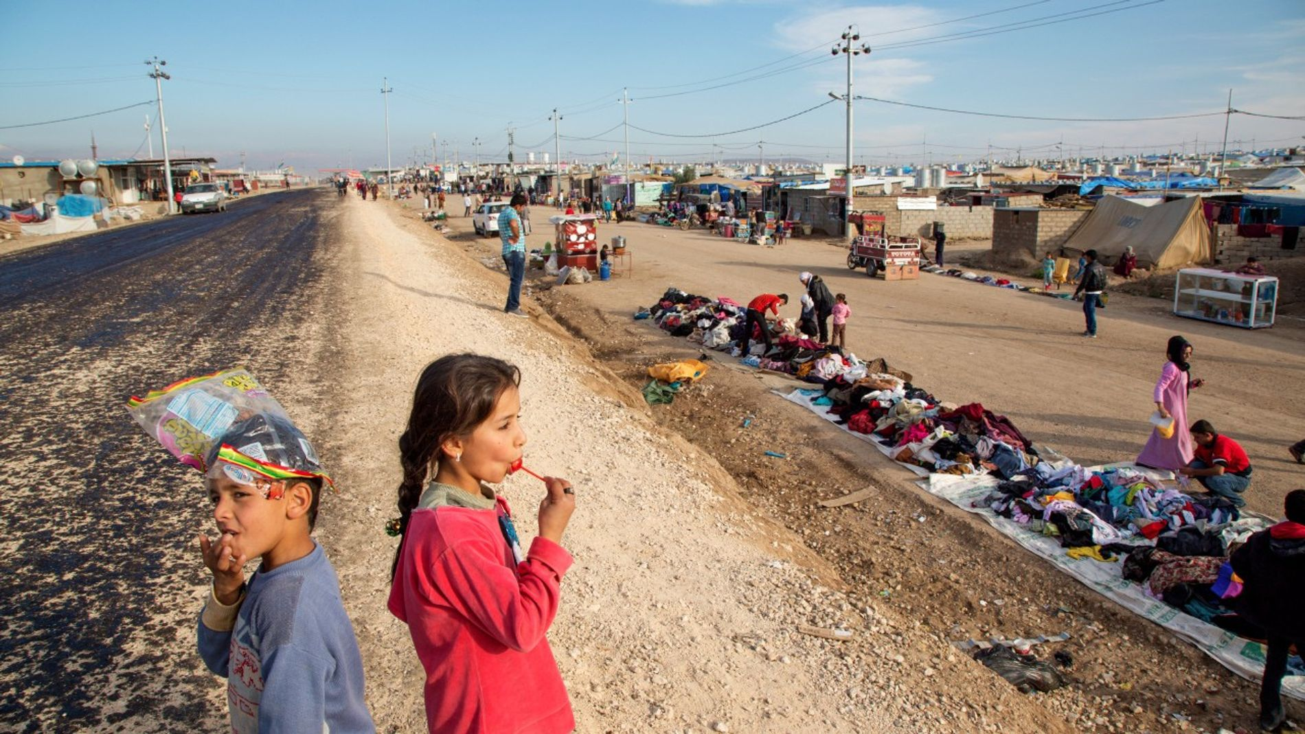 Une petite fille se régale d'une sucette tout en observant le camp de réfugiés de Domiz, ...