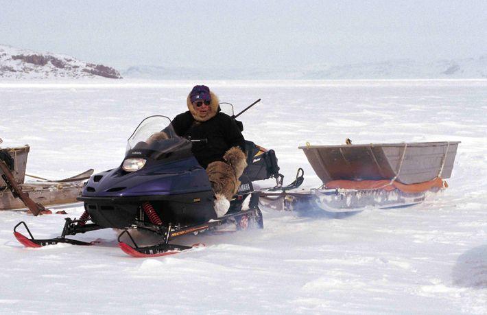 Un chasseur de phoque se déplace en motoneige sur la banquise de Cape Dorset, dans le ...