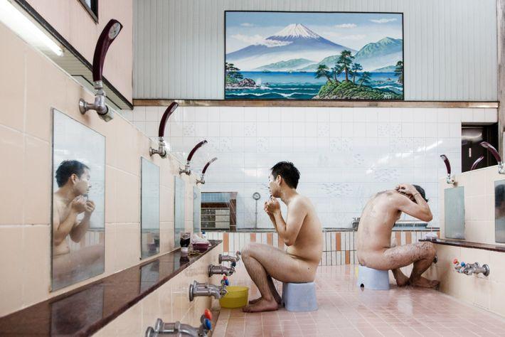Fidèles à la tradition, des Tokyoïtes se préparent avant de plonger dans les eaux chaudes du ...