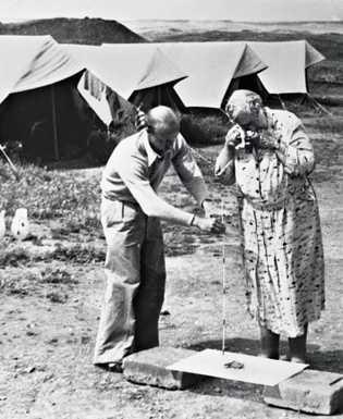 Agatha Christie photographie une des très nombreuses pièces d'ivoire finement taillées de Nimrud.