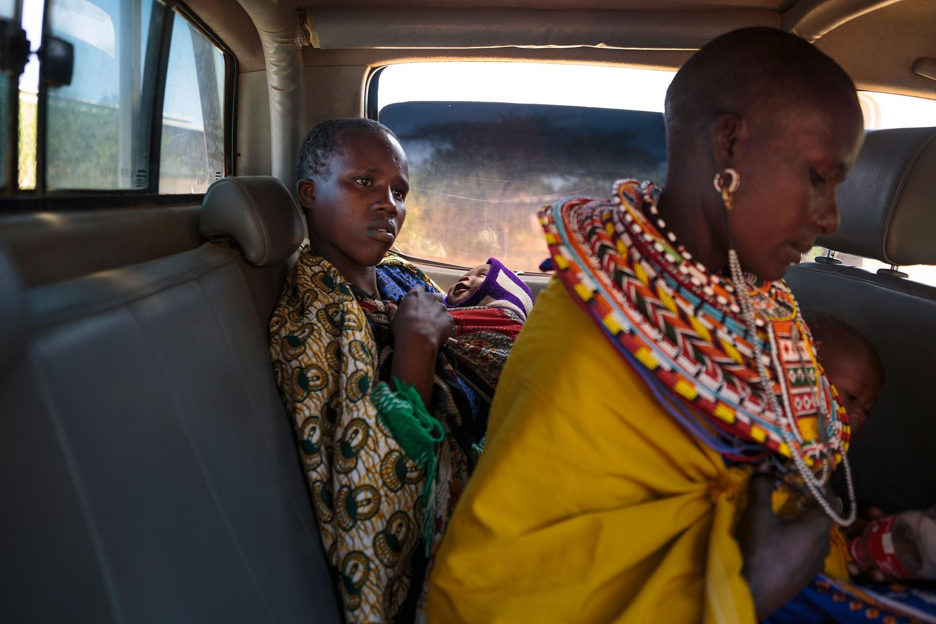 Deux jeunes mères tiennent leurs bébés à l'arrière d'une camionnette de la Samburu Girls Foundation. L'association a négocié avec les chefs de la communauté du village de Oldinyiro, dans le comté d'Isiolo au Kenya, le droit de les emmener dans leur refuge. Les jeunes femmes s'étaient enfuies de leurs domiciles après que leurs bébés furent menacés de mort. Elles avaient été « perlées », selon une coutume qui sert de fiançailles sexuelles durant lesquelles les mères n'ont pas le droit de tomber enceintes. Si c'est le cas, elles subiront soit un avortement grossier, soit la mise à mort du bébé.