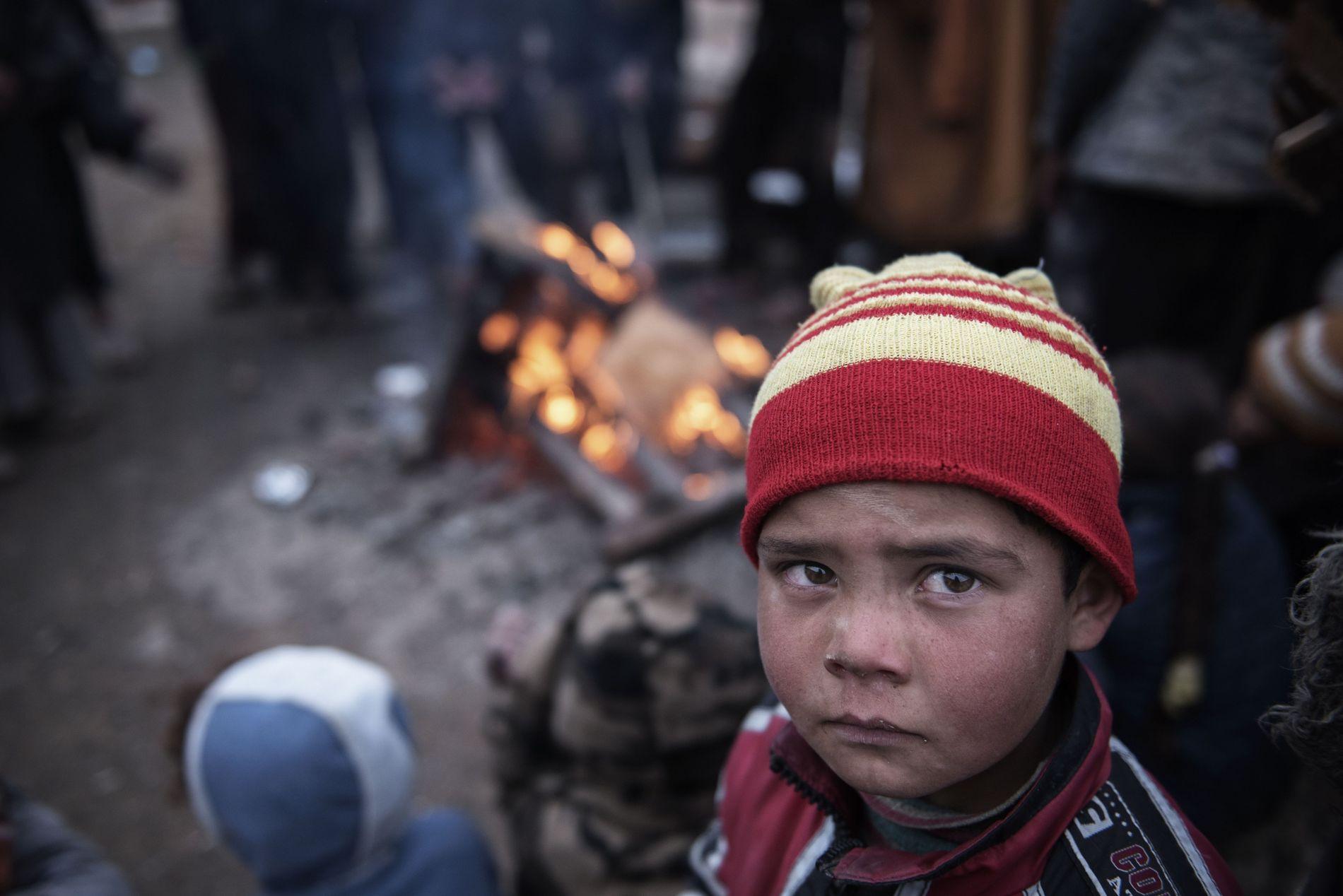 Dans la cour d'une maison, un enfant se tient près d'un feu de camp pour se ...