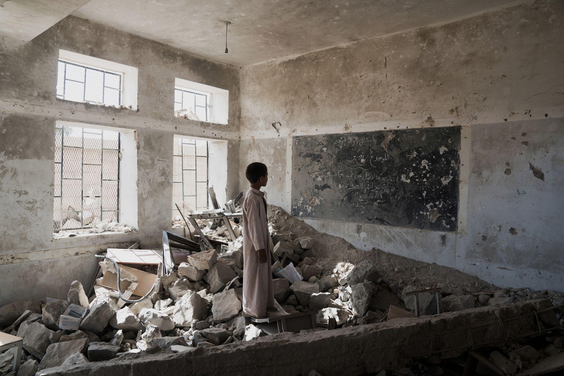 Un étudiant se tient dans les ruines d'une des anciennes salle de classe de l'école Aal ...