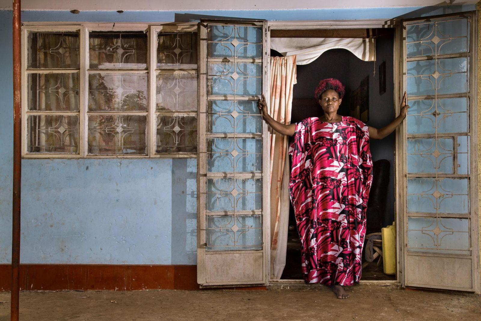 OUGANDA Une semaine après la mort de son mari, Solome Sekimuli, 54 ans, se tient devant la maison ...