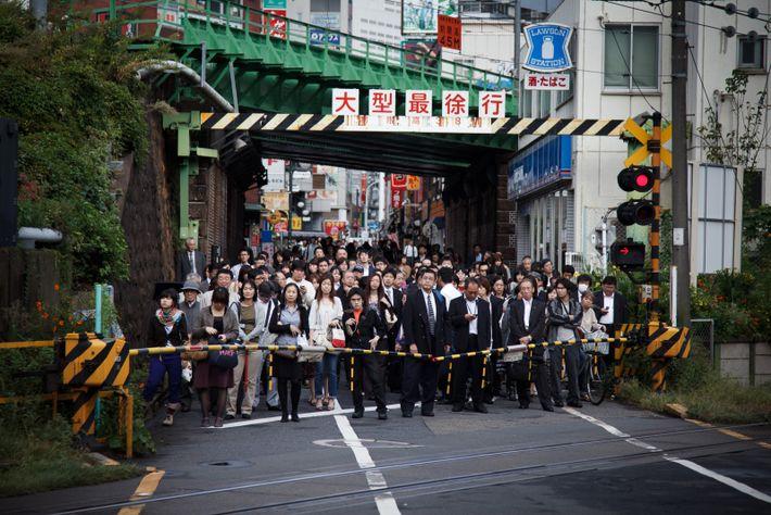 Autour de la gare de Yoyogi, la foule attend l'ouverture d'un passage à niveau.