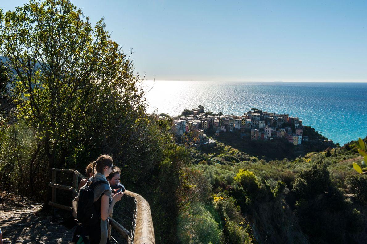 Des marcheurs contemplent Corniglia sur le sentier qui relie le village à Vernazza.  Une randonnée ...