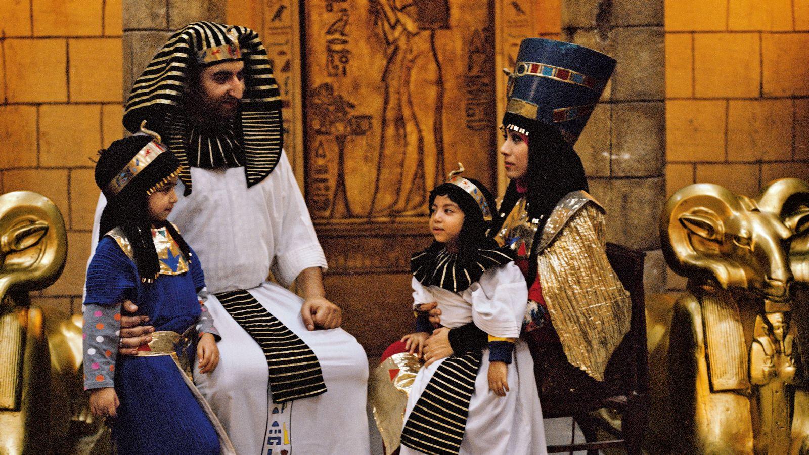 De nos jours, dans un parc à thème du Caire, des Égyptiens prennent des poses évoquant ...