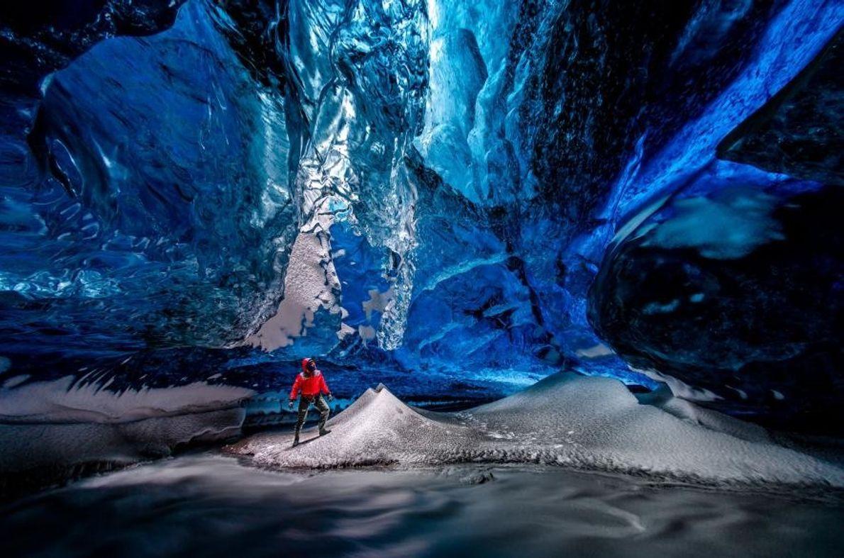 À Vatnajökull, en Islande, un randonneur se trouve à l'intérieur d'une cavité glaciaire.