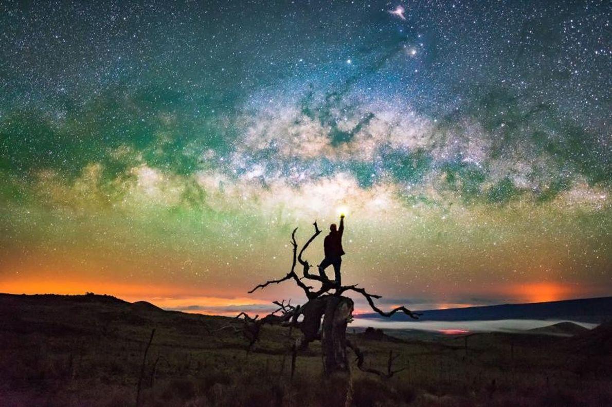 Sur le volcan Mauna Kea, situé sur l'île d'Hawaï, un homme se tient debout sur un ...