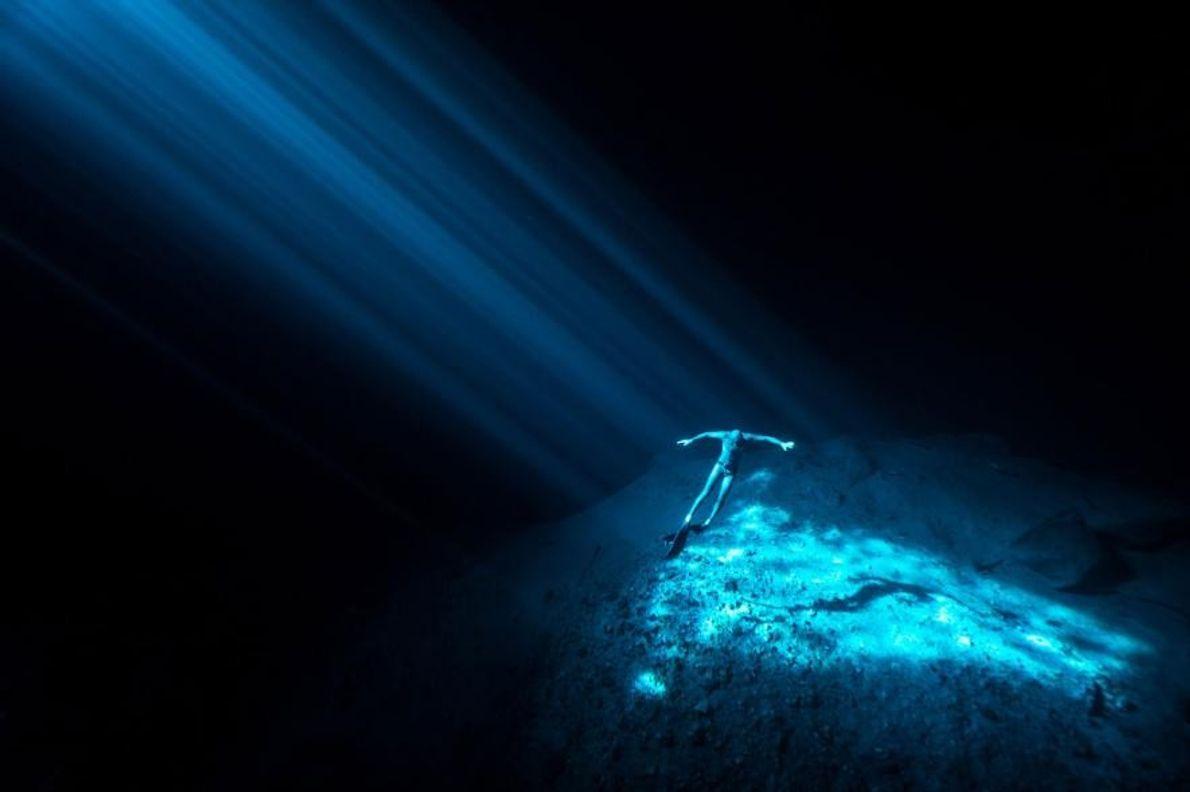 Un plongeur en apnée flotte au cœur du cénote de Nay Yah, une doline sous-marine située ...