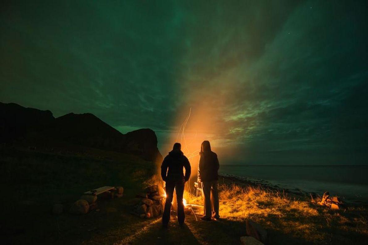 En Norvège, des voyageurs sont absorbés par le ciel étoilé et ses aurores boréales.