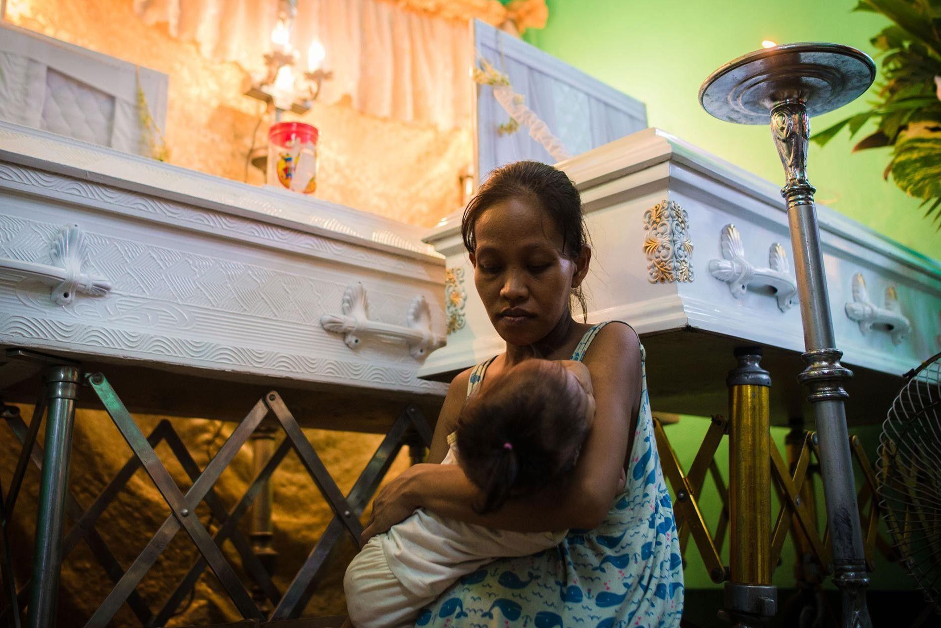 Alors enceinte, Elizabeth Navarro, 29 ans, berce son enfant âgé d'un an pendant la veillée funèbre ...