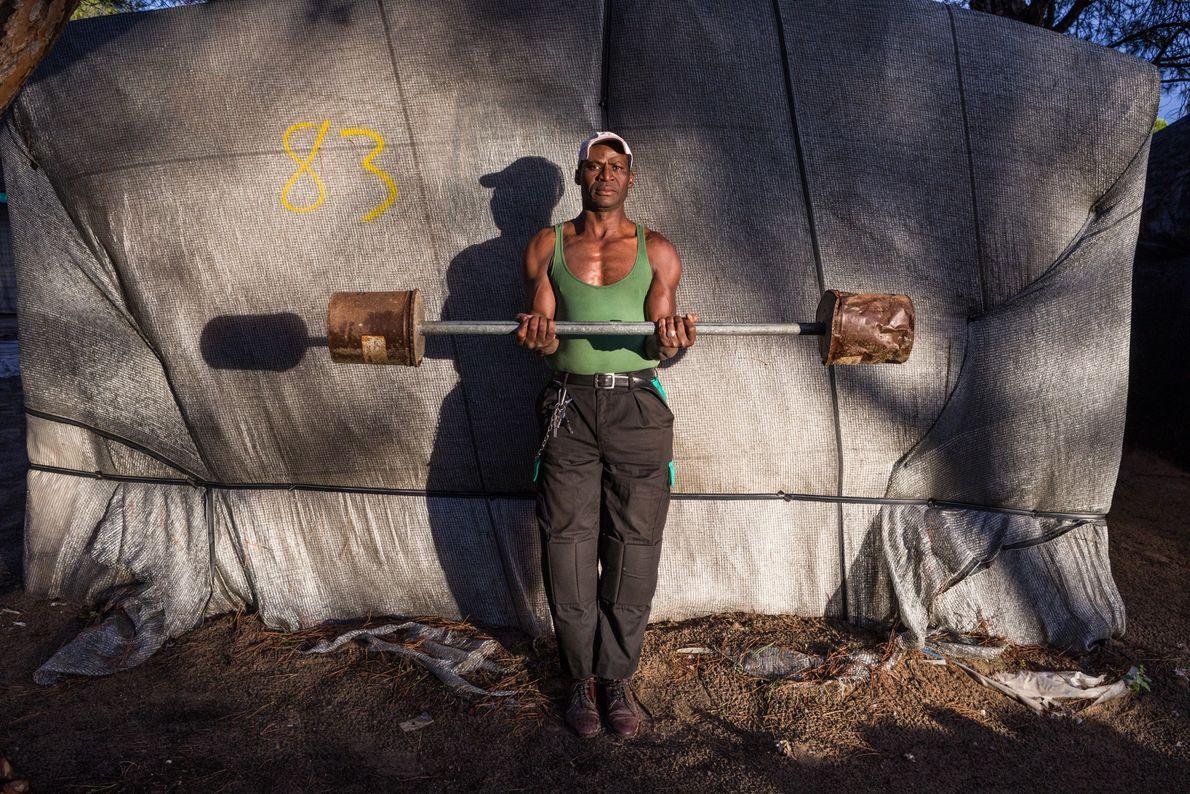 Âgé de 50 ans, Issa Diakite prend la pose avec les haltères qu'il a lui-même fabriquées, ...