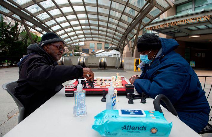 Deux hommes jouent aux échecs devant le George Washington University Hospital à Washington, fin mars. Le ...