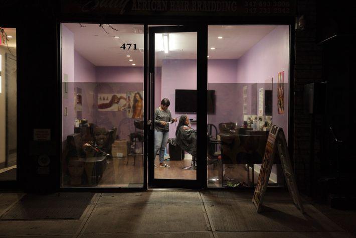 Une femme se fait tresser les cheveux dans un salon du quartier de Bedford Stuyvesant à ...