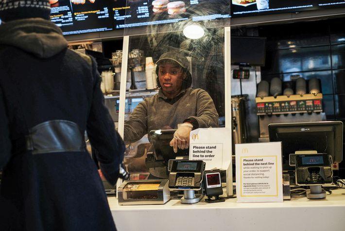 Cet employée d'un McDonald's de Brooklyn, à New York, prend les commandes derrière une vitre.