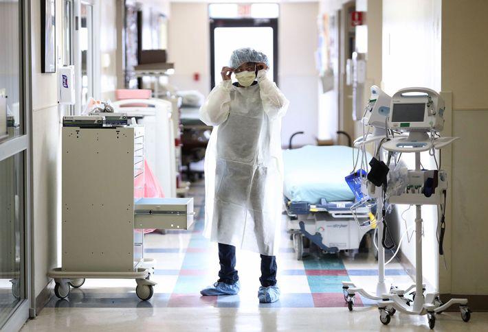 Une infirmière des urgences enfile ses équipements de protection personnelle avant d'entrer dans la chambre d'un ...