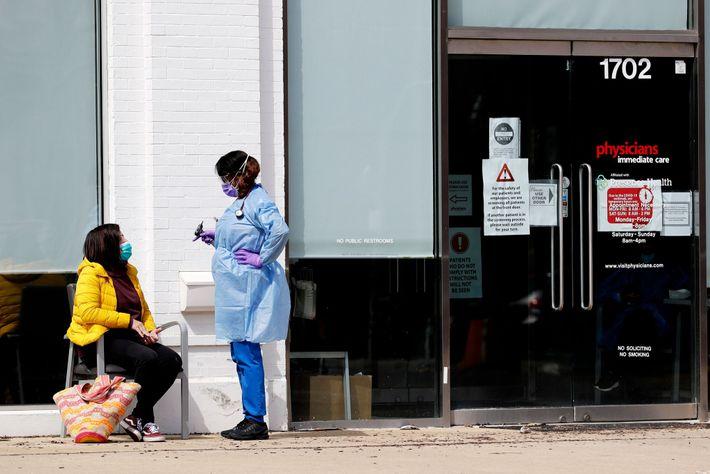 Une soignante discute avec une patiente devant les locaux de l'organisme Physicians Immediate Care à Chicago.