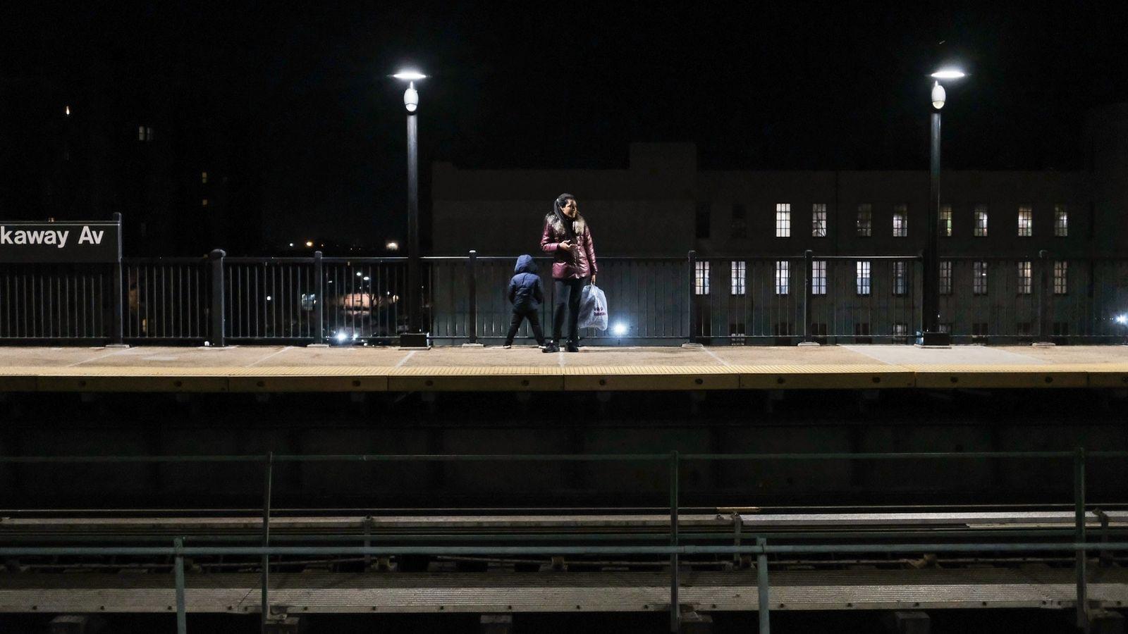 Une femme et son enfant attendent le métro à la station Rockaway Avenue dans le quartier ...