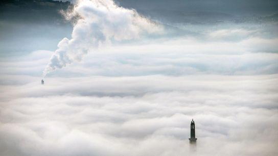La fumée d'une centrale de chauffage urbain s'élève au-dessus des nuages, à Grenoble.