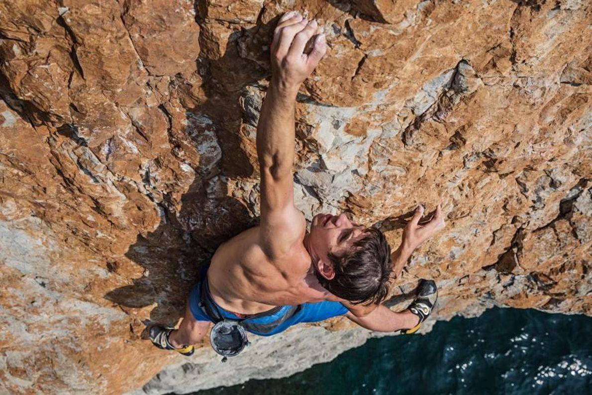 Sur cette photo, Alex Honnold escalade une falaise s'élevant au-dessus du golfe d'Oman. Si escalader une ...
